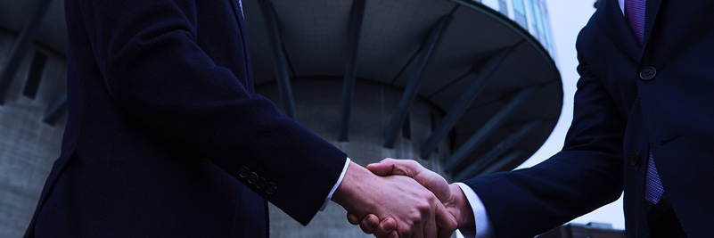 Two men in suits shaking hands