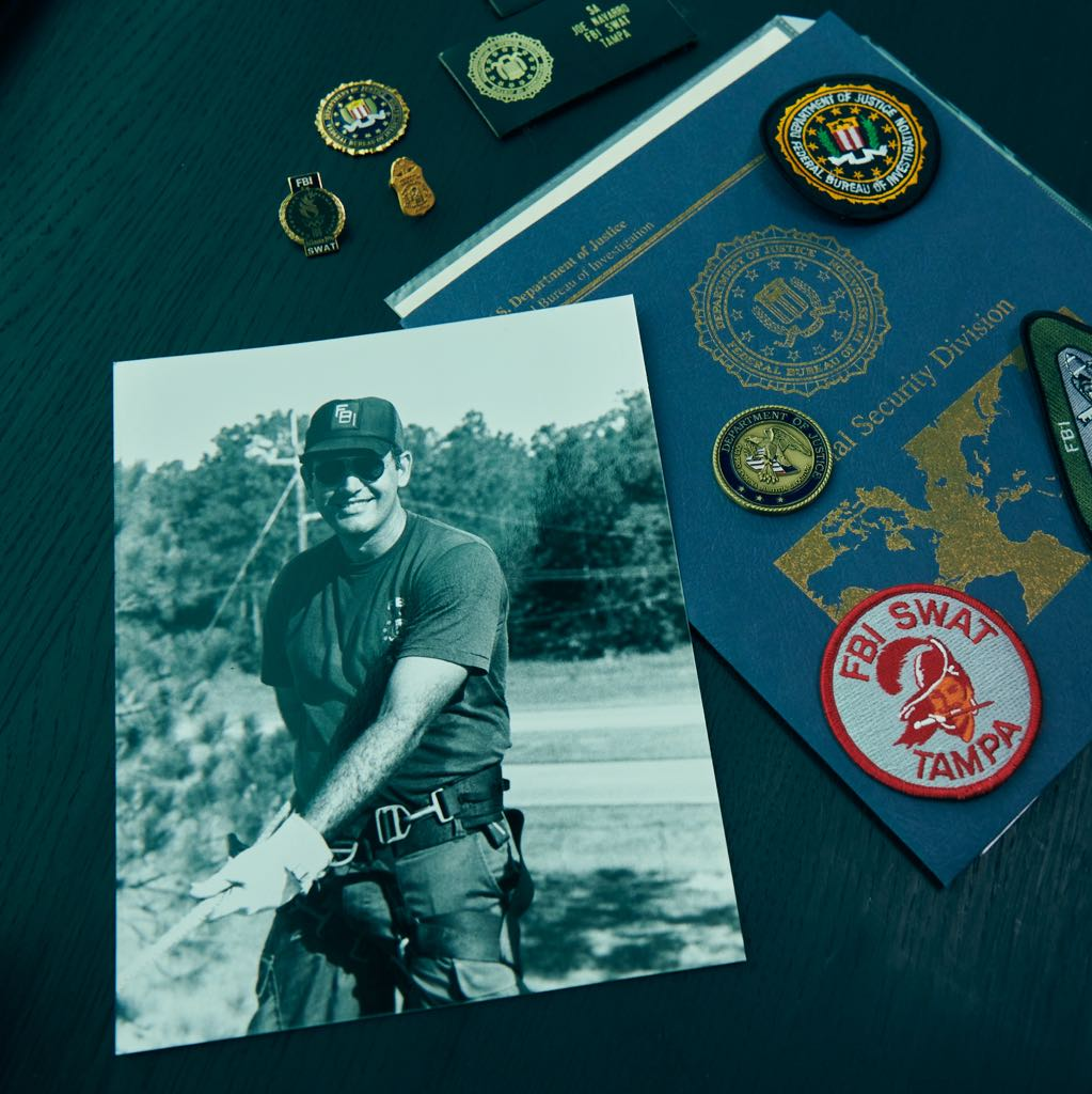 Photo of a man, a folder and different badges on a table